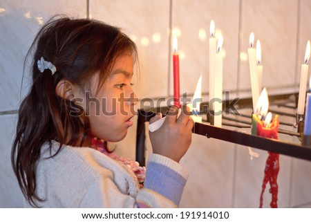 SUCRE, BOLIVIA - JANUARY 18, 2012: A girl lights a candle inside a little improvised chapel. January 18, 2012. in Sucre, Bolivia. the vast majority of Bolivian people are Roman Catholics. - stock photo