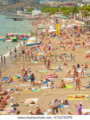 SUDAK, UKRAINE - SEPT 08, 2015: People at a sea beach in Sudak. According to National Geographic, Crimea was among the top 20 travel destinations in 2013