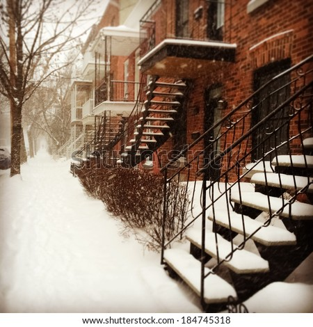 Sudden snowstorm in Montreal. Red brick buildings with staircases covered by snow. - stock photo