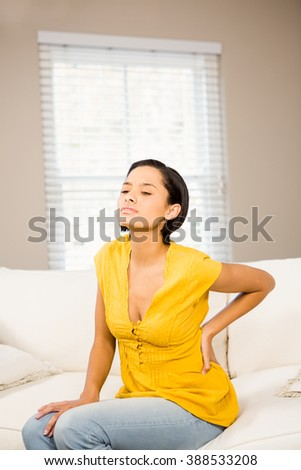 Suffering brunette touching her back while sitting on the sofa - stock photo
