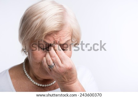 Suffering from headache. Closeup portrait of elderly woman touching her nose suffering from pain while standing against white background - stock photo