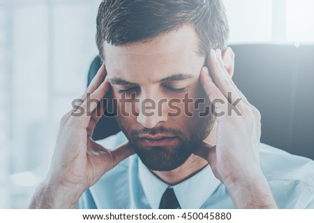 Suffering from headache. Depressed young man in shirt and tie holding head in hands and keeping eyes closed while sitting at his working place
