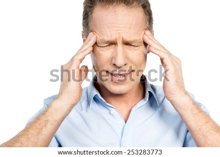 Suffering from headache. Frustrated mature man touching head with fingers and keeping eyes closed while standing against white background