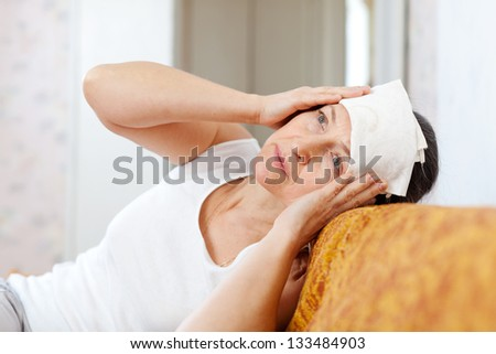 Suffering mature woman stupes  towel to her head