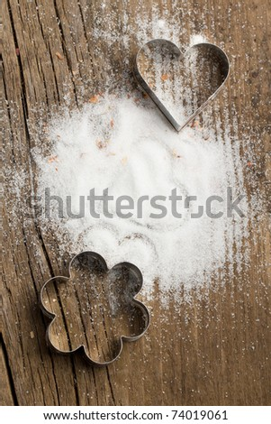 Sugar and cookie cutters as heart and flower on old wooden table. See series. - stock photo