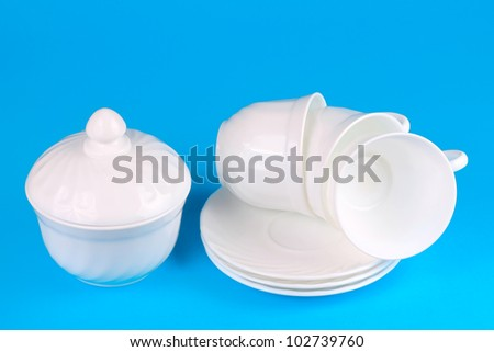 Sugar bowl with cups on saucer isolated on blue