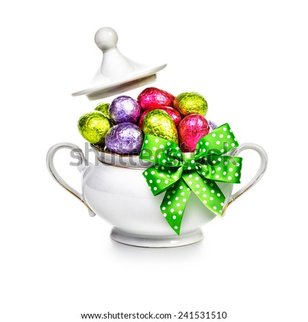 Sugar bowl with ribbon bow full of chocolate candy eggs wrapped in foil on white background. Easter themes - stock photo