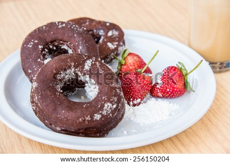 Sugar chocolate donuts and fresh strawberries and ice coffee