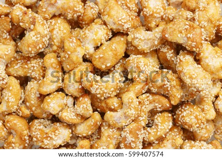 Sugar coated cashew nuts with white sesame for background