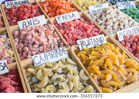 Sugar coated fruit gums (sweets, candy) on display in Spain. The hand written labels read as follows: Blueberry, aniseed, strawberry, rice with milk, Limon verde, Caipirina, Banana, Peach,