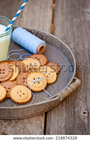 Sugar cookies in shape of buttons on wooden table with a glass of milk. Also available in horizontal format.  - stock photo