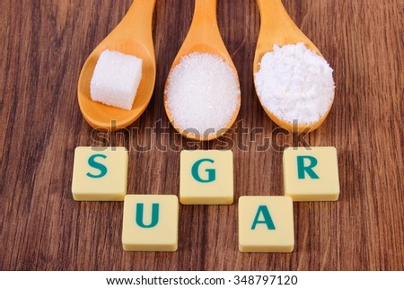 Sugar cube, granulated and powdered sugar on wooden spoons with text sugar, ingredient for cooking or baking - stock photo