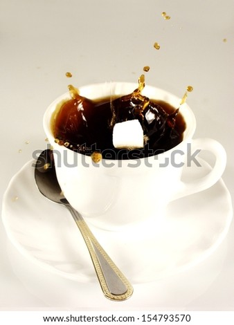 Sugar cubes falling into the coffee - stock photo
