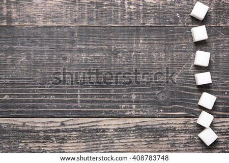 Sugar cubes on a brown wooden background - stock photo