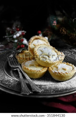 Sugar frosted festive mince pies in a rustic setting with a dark background. Accommodation for copy space. The perfect cover image for your Christmas or Thanksgiving dessert menu design. - stock photo