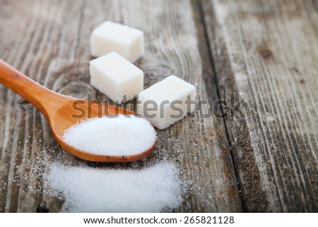 Sugar in a spoon on old brown table . - stock photo