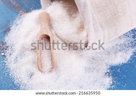 Sugar in bag on color wooden background - stock photo