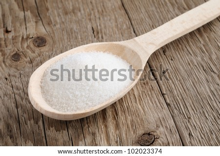 Sugar in spoon on wooden background - stock photo
