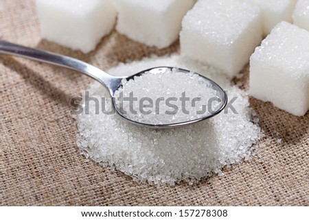Sugar is in the spoon on the table - stock photo