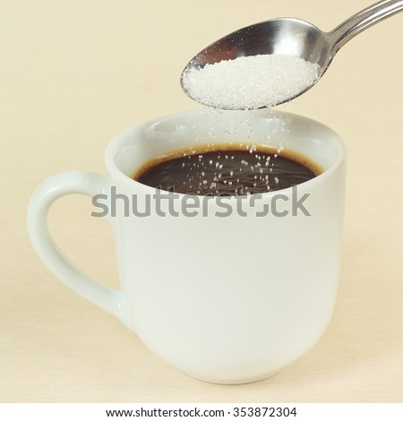 Sugar is poured from a spoon in a coffee cup - stock photo