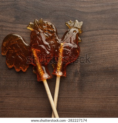 sugar lollipops rooster shaped on wooden table - stock photo