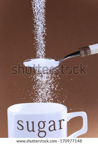Sugar on brown background - stock photo