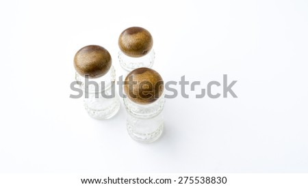 Sugar, salt and pepper shakers or storage glass jars with a wooden stand or container cap. Isolated on white background.