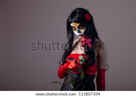 Sugar skull girl holding red rose, Day of the Dead Halloween theme - stock photo