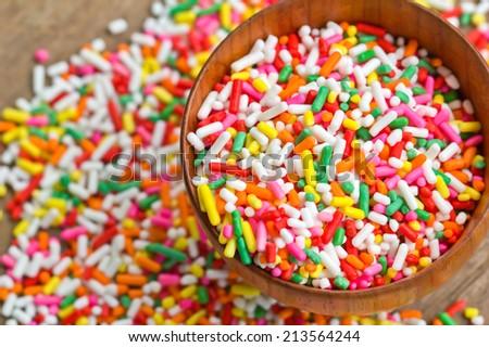 Sugar sprinkles in wood bowl - stock photo