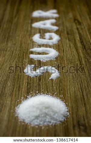 sugar text written with sugar crystals on table - stock photo