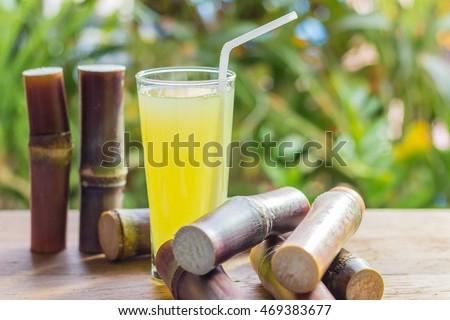 Sugarcane fresh juice with piece of sugarcane on wooden background. Closeup image / Selective focus