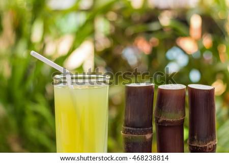 Sugarcane juice with piece of sugarcane on wooden background