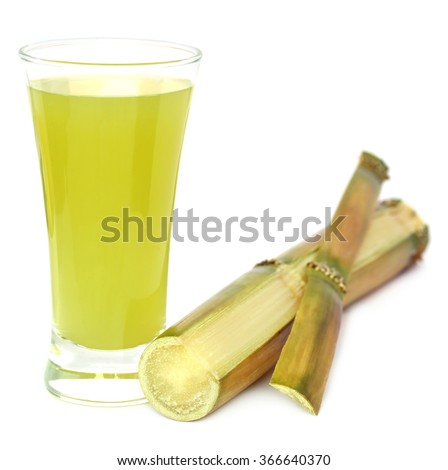 Sugarcane with juice in a glass over white background