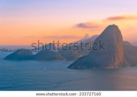 Sugarloaf Mountain from Behind during Red Sunset with View of Hills and Ocean, RIo de Janeiro, Brazil - stock photo