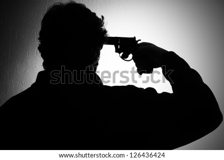 suicide, a man put a gun to his head, black and white - stock photo