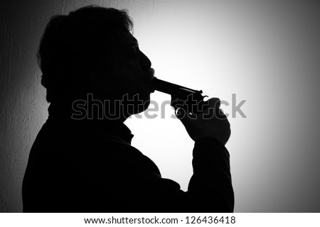 suicide, a man stuck a gun in his mouth, black and white - stock photo