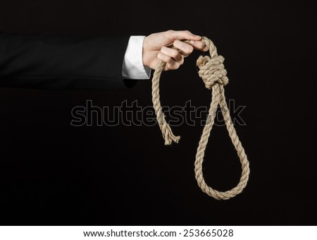 Suicide and business topic: Hand of a businessman in a black jacket holding a loop of rope for hanging on a black isolated background