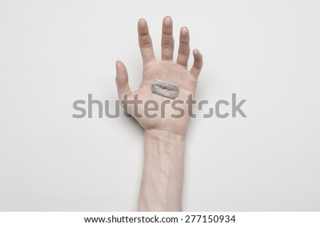 Suicide and Halloween theme: the human hand holding the blade to suicide isolated on white background in studio top view - stock photo