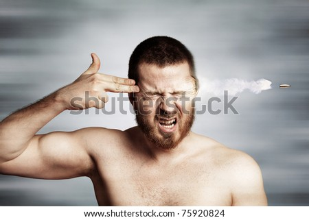 Suicide concept - young man killing himself metaphorically - stock photo
