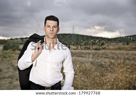 Suit man posing in dramatic cloudy sky - stock photo