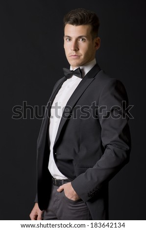 Suit man posing over black background