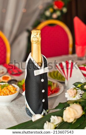 Suit of the groom on a bottle with champagne.