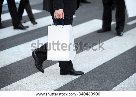 Suit walking with white shopping bag on street pedestrian.