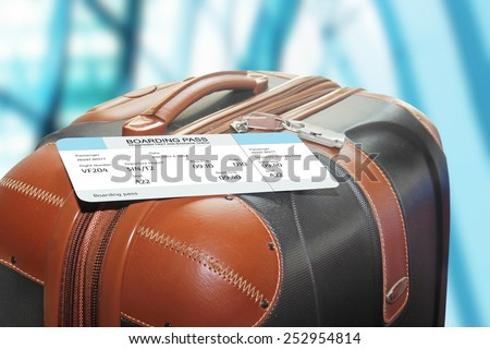 suitcase and boarding pass at the airport - stock photo