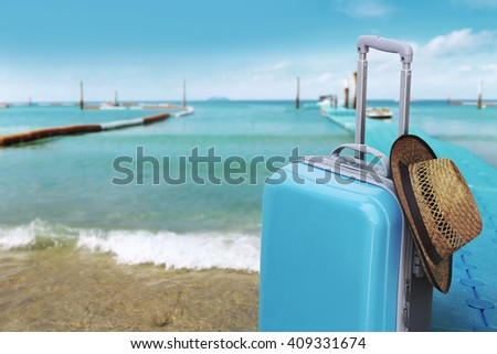 Suitcase and Hat in front of the sea Travel and holiday ideas  - stock photo