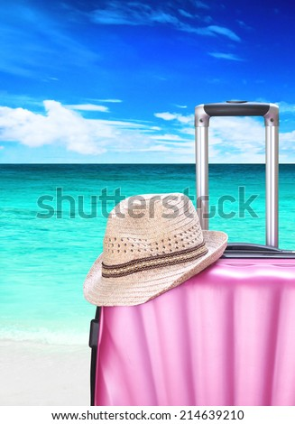 suitcase and hat on the beach - stock photo