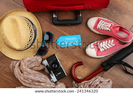 Suitcase and tourist stuff with inscription travel insurance on wooden background - stock photo