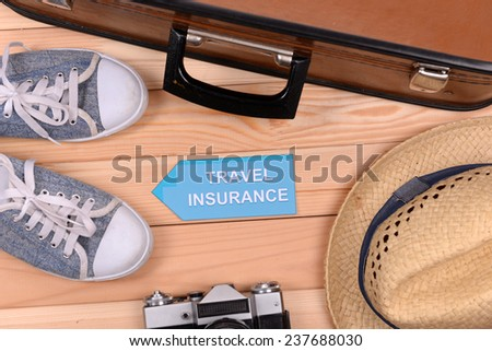 Suitcase and tourist stuff with inscription travel insurance on wooden background top view - stock photo