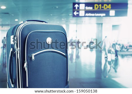 Suitcase at the airport. Toned - stock photo