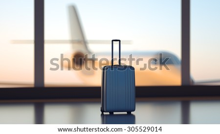 Suitcase in front of airport windows with plane on background - stock photo